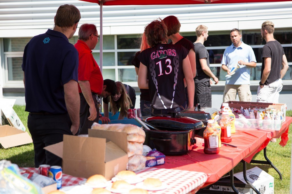 Davis GMC Buick volunteers cook for a charity BBQ in support of the Bow Island Senator Gershaw School.